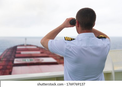 Navigator on the bridge of a large bulk carrier, doing lookout at the horizon with his binoculars