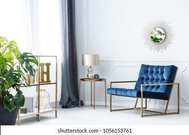 Navy blue armchair next to table with gold lamp in elegant living room interior with mirror