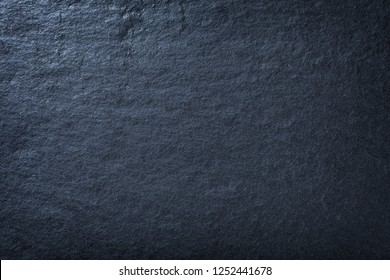 Navy blue background of natural slate. Texture of stone closeup. Graphite backdrop macro
