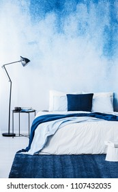 Navy blue carpet in front of bed next to lamp in bedroom interior with wallpaper