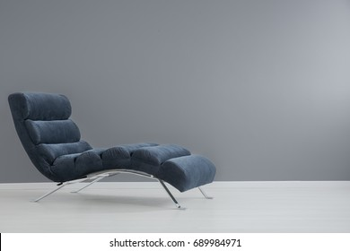Navy blue chaise lounge with metallic elements in spacious apartment