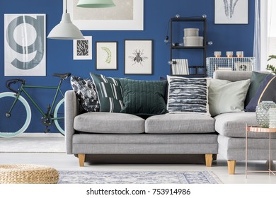 Navy blue hipster living room with green bicycle and simple corner sofa