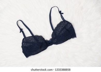Navy blue lace bra on white fur. Flat lay. Fashion lingerie concept.