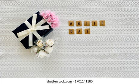 Navy blue present box, flowers and English letters on the lace background top right