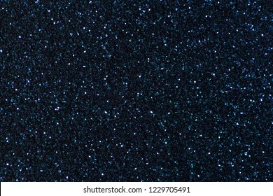 Navy blue sparkling background from small sequins, closeup. Brilliant shiny backdrop from textile. Shimmer denim paper