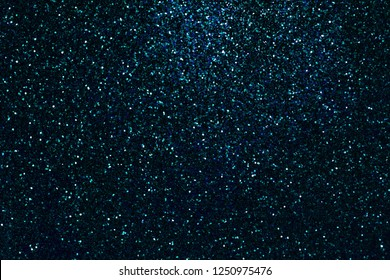 Navy blue sparkling background from small sequins, closeup. Brilliant turquoise shiny backdrop from textile. Shimmer denim paper