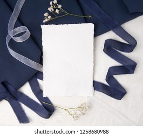 Navy blue wedding invitation mockup with silk ribbons and greenery.