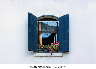 navy blue wooden shafts, open glass windows made from old brown structure, with green plant, red flowers and white curtains