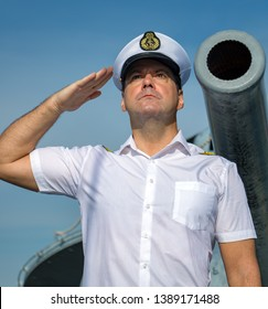 A navy officer standing under a ship's cannon and do salute.The captain in white uniform stands aboard a ship and saluting.
