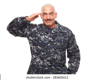 Navy sailor or chief grinning while saluting on white background.