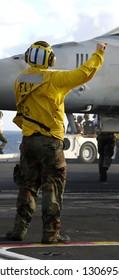 A Navy sailor directs an F-18 fighter aircraft around the flight deck on an aircraft carrier