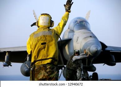 A Navy Sailor directs an F-18 Hornet fighter aircraft around the flight deck of an aircraft carrier