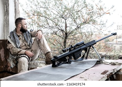 Navy SEAL sniper in battle uniform and shemagh on shoulders, sitting near large caliber sniper rifle with optics sight, on firing position in abandoned building. Urban warfare on Middle East company