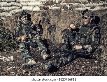 Navy SEALs soldiers, special operations forces fighters in camouflage uniform, body armor and helmet, armed assault rifles, sitting in trench, resting after fight, talking and joking with comrades