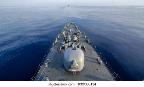 """Navy ship sailing along the calm sea ,view from bow. The phase behind gun turret is Thai language it's a caution for operators mean """"Caution Gun may turn without any notice"""""""