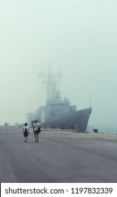 A navy US ship in the naval base moored in the fog