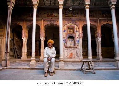 NAWALGARH, INDIA - FEB 6: Lonely happy senior in indian turban sitting under ancient columns of palace on February 6, 2015. With popul. of 100,000, Nawalgarh is education center of Shekhawati region