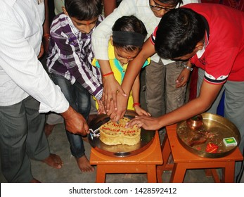 Nawalgarh, Rajasthan/India-November 04, 2012: Indian family celebrating birthday. A little girl fleming the candles and cutting a cake on her birthday at Nawalgarh near Jaipur, Rajasthan.
