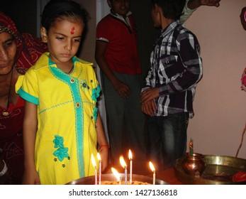 Nawalgarh, Rajasthan/India-November 04, 2012: A little girl fleming the candles before cutting a cake on her birthday at Nawalgarh near Jaipur, Rajasthan.
