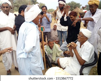 Nawalgarh/India-Sept 19, 2019: Farmers entertaining themselves to the tune of Bassoon at the famous animal fair of Nawalgarh.