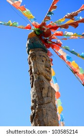 Naxi tribe totem pole attached with colorful Tibetan prayer flags in Dongba Valley, Lijiang, Yunnan Province of China.