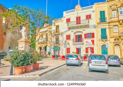 NAXXAR, MALTA - JUNE 14, 2018: The scenic square with historical edifices with bright red windows and shutters and the cafe on the ground floor, on June 14 in Naxxar.