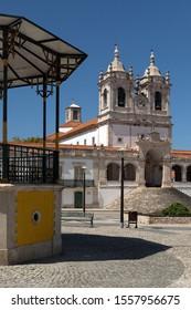 NAZARE, PORTUGAL - AUGUST 30, 2019: Nossa Senhora da Nazare Church, Sanctuary, with the bandstand in foreground, Nazare, Portugal.