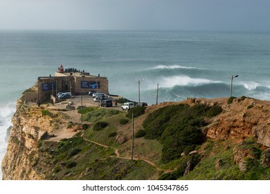 NAZARE, PORTUGAL - December 16, 2016: Spectators watch XXL waves from the Archangel St Michael fort on the Praia do Norte beach in Nazare, Portugal on December 16, 2016.
