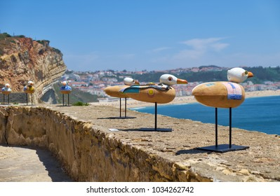 NAZARE, PORTUGAL - JUNE 26, 2016: An installation art on the Nazare Lighthouse (Farol da Nazare) - the seagulls seating on the parapet with Nazare town on background.  Portugal