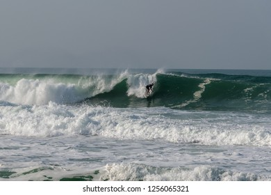 NAZARE, PORTUGAL - NOVEMBER 15 : surfer exercises on big Atlantic ocean wave next to Nazare, Portugal north beach on November 15, 2018.