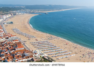 Nazare in Portugal in summer, beach and tiles roofs, people in holidays
