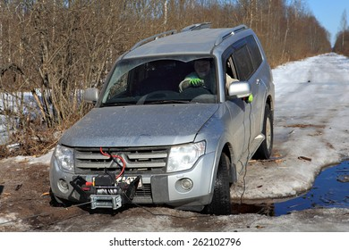 Nazia, Leningrad Region, Russia - March 17, 2015: The driver controls the winch while sitting in  passenger compartment of  car, passenger car wheels fell into  pit road, on  road spring melts  ice.