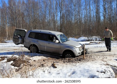 Nazia village, Leningrad Region, Russia - March 17, 2015: Vehicle is stuck in a hole in the winter forest road, the driver install a winch to rescue the car.