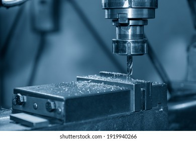 The NC milling machine drilling  at the metal part by flat drill tools. The shop floor operation by NC milling machine.