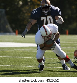 NCAA College Football.  The defender dives onto running back from behind.