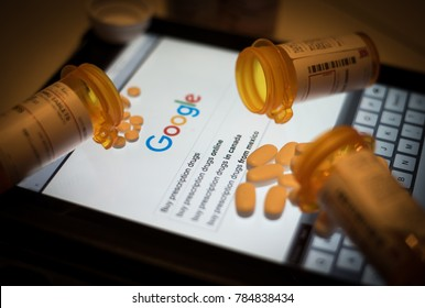 NC/USA- 1/2/2018: Prescription drugs and bottles lay strewn upon an electronic table, while the Google search engine awaits further user input.
