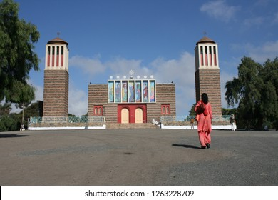 Nda Mariam Orthodox Church in Asmara Eritrea on pretty day with white Clouds and blue sky and person in the foreground