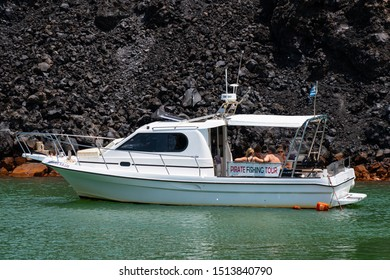 Nea Kameni Island, Greece - July 16 2019:   holiday makers relax in the back of a cabin cruiser anchored in the blue green waters of Nea Kameni island in Santorini