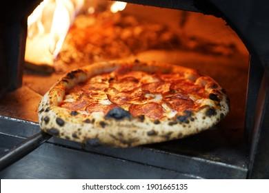 pizza napolitaine avec saucisse dans un four à bois