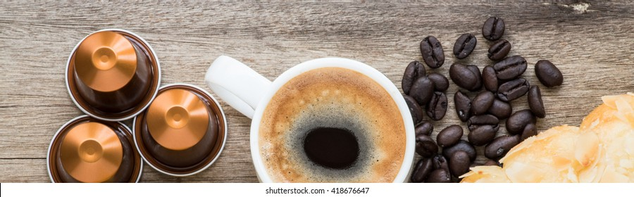 Neapresso capsule and  espresso cup with wooden background.