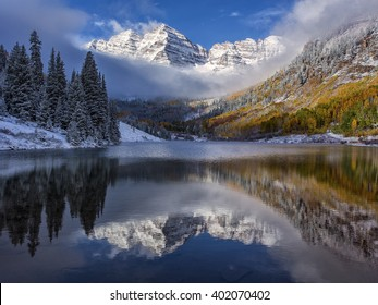 Near Aspen, Colorado, the Maroon Bells receives a layer of snow during the fall colors. An early morning photo taken with the clearing clouds.