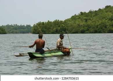 Near Bentota, Sri Lanka - April 18th 2011: Two fishermen sitting in a traditional dugout canoe and fishing with fishing rods on a river