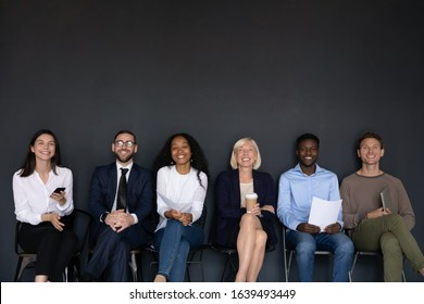 Near black wall studio background sitting six diverse happy entrepreneurs, successful corporate staff members, businesspeople ready for negotiation, wait for job interview sit in row queue, hr concept