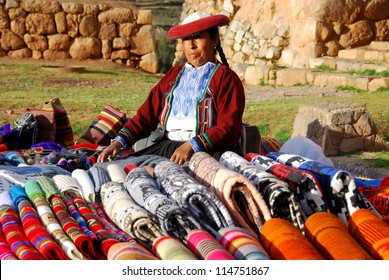 NEAR CUSCO PERU-NOVEMBER 15:Quechua woman dressed in traditional clothing sale colorful tablecloths and fabric on November 15, 2010 in Cusco Peru. The national rural poverty rate is over 50 per cent.