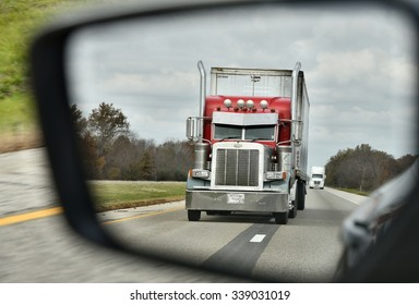NEAR DALLAS, TX/USA - NOVEMBER 4, 2015: Peterbilt Truck seen in the rearview mirror