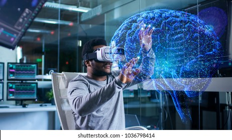 In Near Future Laboratory Scientist Wearing Virtual Reality Headset Sitting in a Chair Using Futuristic Holografic Interface. Modern Brain Study/ Neurological Research Center.