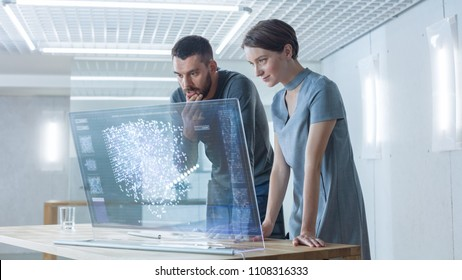 In the Near Future Male and Female Computer Engineers Talk While Working on the Transparent Display Computer. Screen Shows Interactive Neural Network, AI Project, Futuristic User Interface.
