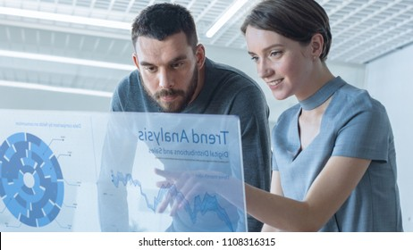 In the Near Future Male and Female Trade Agents Talk While Working on the Transparent Display Computer. Screen Shows Economical Graphs, Analysis of Trade, Futuristic User Interface.