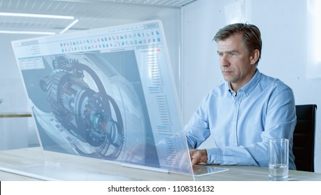 In the Near Future Professional Engineer Works on Transparent Computer Display, Constructing 3D Model of the Metal Detail. He Works in a Bright and Modern Office.