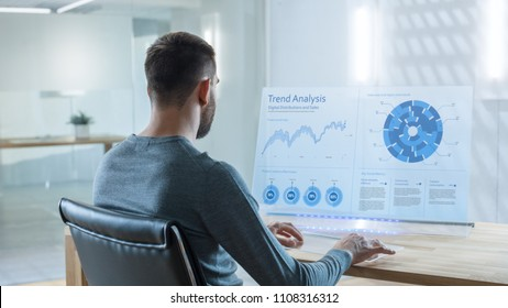 In the Near Future Trade Worker Analyzes Trade Markets on His Transparent Computer Display. Screen Show Interactive User Interface with Statistics, Graphs and Charts. Office is Bright and Modern.